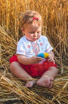 Dziecko w polu pszenicy. w wyszywance koncepcja dnia niepodległości ukrainy. selektywne skupienie. dziecko.