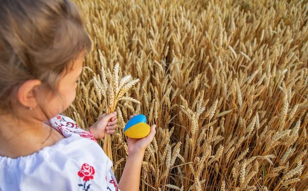 Dziecko w polu pszenicy. w wyszywance koncepcja dnia niepodległości ukrainy. selektywne skupienie.