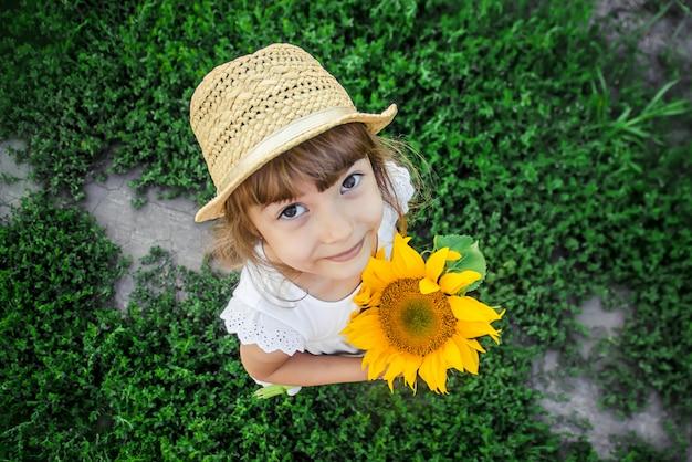 Dziecko w polu słoneczników to mały rolnik. selektywna ostrość.
