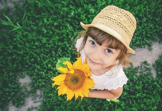 Dziecko w polu słoneczników to mały rolnik. selektywne skupienie.