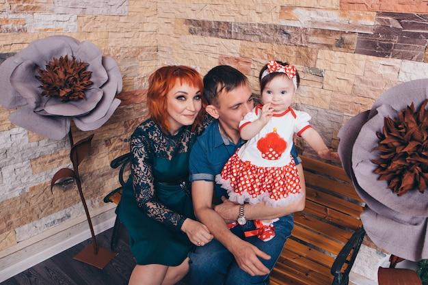 Dziecko w ramionach matki i ojca. kobieta, mężczyzna z dzieckiem w ramionach obok dużego kwiatu