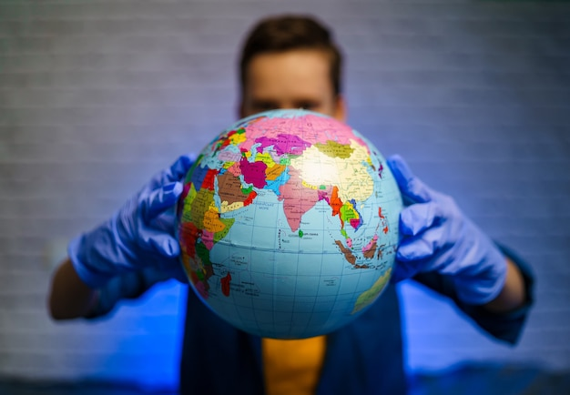 Dziecko w rękawiczkach medycznych trzyma globus. mały chłopiec myśli o pandemii i wirusie. pojęcie covid-19 i koronawirusa.