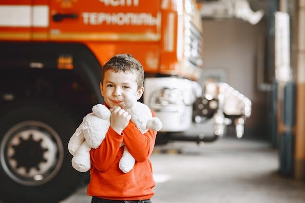 Dziecko w remizie. chłopiec z zabawką. dziecko w pobliżu wozu strażackiego.