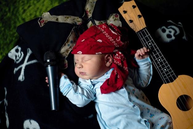 Dziecko w rockowej bandanie leży z gitarą i mikrofonem