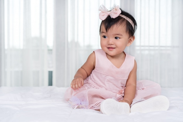 Dziecko w różowej sukience na łóżku