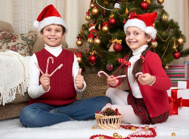 Dziecko w santa hat bawić się w pobliżu udekorowanej choinki w domu szczęśliwe emocje