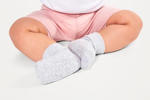 Dziecko w skarpetkach siedzi na podłodze