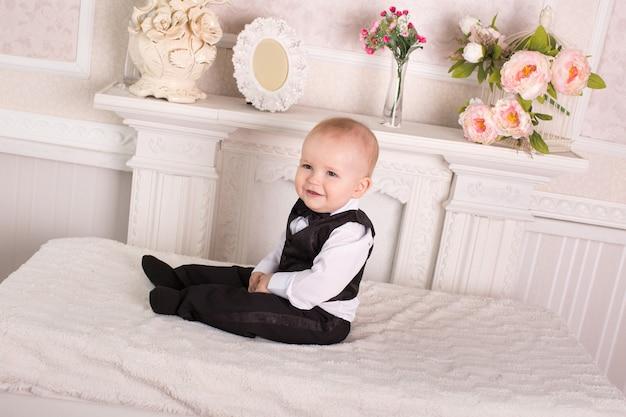 Dziecko w smokingu, siedzące na łóżku przy kominku. pan młody.
