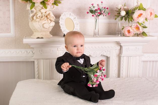 Dziecko w smokingu siedzące na łóżku przy kominku z kwiatami w dłoniach.