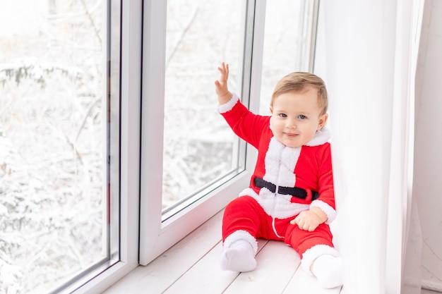 Dziecko w stroju świętego mikołaja na parapecie okna, pojęcie nowego roku i świąt bożego narodzenia