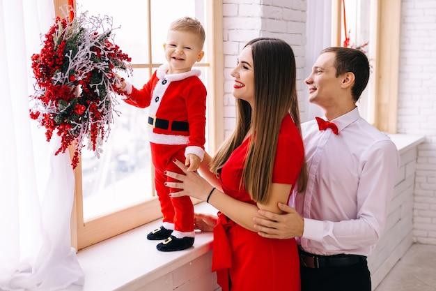Dziecko w stroju świętego mikołaja na parapecie rodzice w świątecznych ubraniach w pobliżu okna i dziecko. wieniec bożonarodzeniowy.