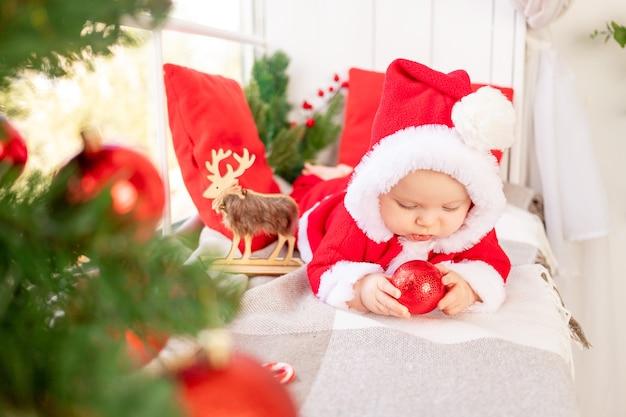Dziecko w stroju świętego mikołaja pod choinką bawi się czerwonymi bombkami leżącymi na oknie domu, koncepcja nowego roku
