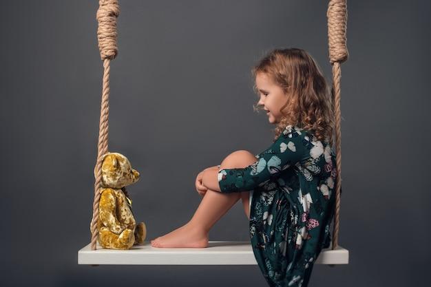 Dziecko w studio pozuje w modnych ciuchach
