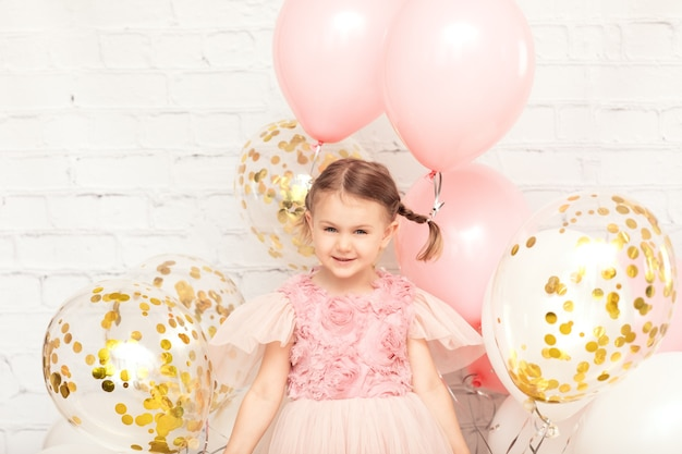 Dziecko w sukience trzyma wiele różowych złotych balonów dostaje prezent na urodziny urodziny wakacje makieta