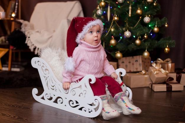 Dziecko w świątecznej czapce w swetrze i wełnianych skarpetkach na sankach we wnętrzu noworocznym emocje