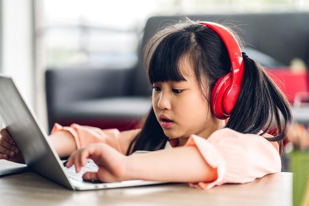 Dziecko w szkole dziewczynka uczy się i patrzy na komputer robiąc pracę domową studiując wiedzę z systemem e-learningu edukacji online.