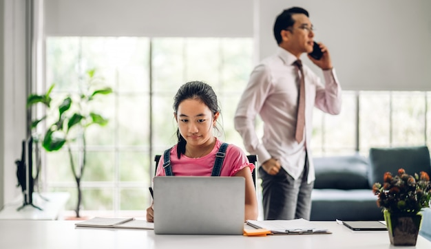 Dziecko w szkole mała dziewczynka ucząca się i patrząca na komputer, odrabiająca pracę domową, studiująca wiedzę za pomocą systemu e-learningowego do edukacji online. konferencja wideo z nauczycielem w domu
