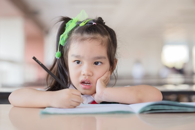 Dziecko w szkole podstawowej myśli o odpowiedzi siedząc przy biurku.