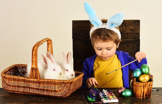 Dziecko w uszy królika maluje pisankę. mały chłopiec z królikiem easters w koszyku.