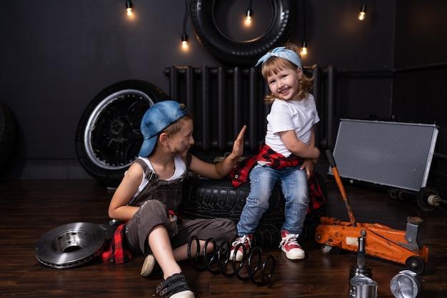 Dziecko w warsztacie samochodowym wśród kół i części samochodowych