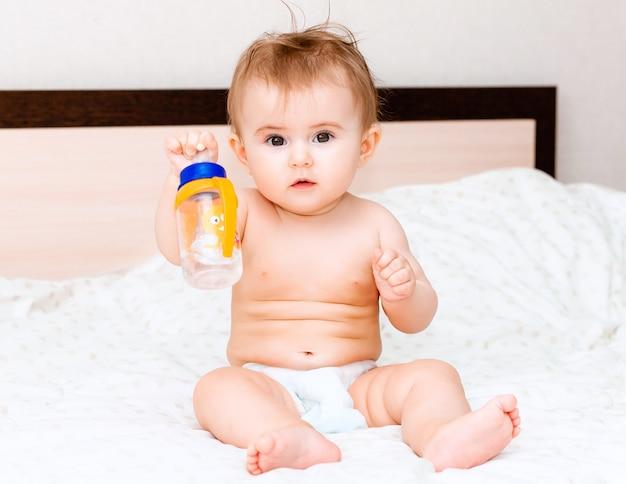 Dziecko w wieku 6 miesięcy pije wodę z butelki leżąc na łóżku. szczęśliwe i radosne dziecko
