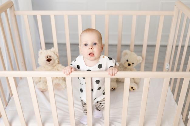 Dziecko w wieku 8 miesięcy stoi w łóżeczku z zabawkami w piżamie po spaniu w jasnym pokoju dziecięcym i patrzy w kamerę, widok z góry, miejsce na tekst