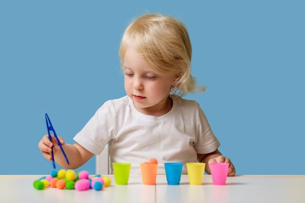Dziecko w wieku dziewczynki bawi się edukacyjną zabawką sortującą w pomieszczeniu