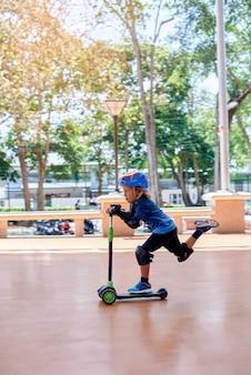 Dziecko w wieku przedszkolnym zabezpieczone sprzętem sportowym jeździ na hulajnodze po drodze ciesząc się wakacjami. sporty ekstremalne i mały chłopiec.