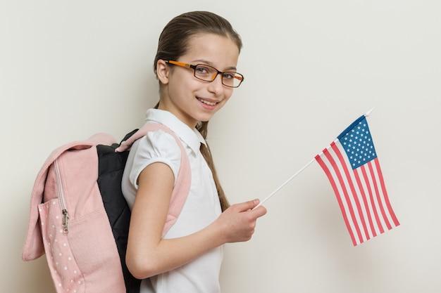 Dziecko w wieku szkolnym z plecakiem trzyma flagę usa