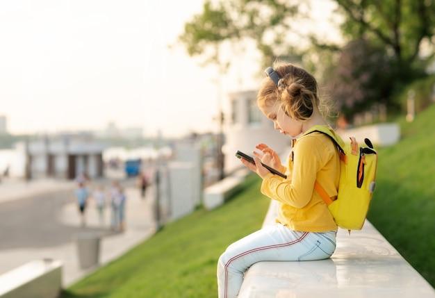 Dziecko w wieku szkolnym z plecakiem w naturze słuchać muzyki za pomocą telefonu komórkowego i słuchawek. komunikacja technologii online. edukacja online w szkole podstawowej. kwarantanna się skończyła. powrót do szkoły.