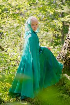 Dziecko w zielonej sukience z kapturem