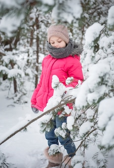 Dziecko w zimie. mała dziewczynka bawiąca się zimą na dworze. piękny portret dziecka zimą. szczęśliwe dziecko, zimowe zabawy na świeżym powietrzu.
