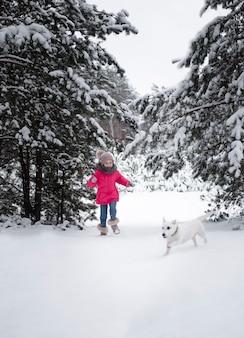 Dziecko w zimie. mała dziewczynka w naturze bawi się z psem zimą