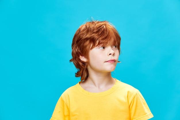 Dziecko w żółtej koszulce wygląda z boku na niebieskim tle na białym tle