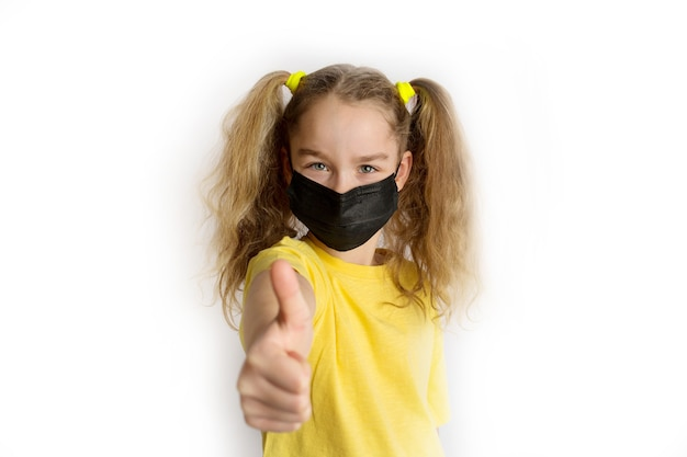 Dziecko w żółtej koszuli w czarnej masce od covid na białym tle. zdjęcie wysokiej jakości