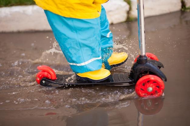 Dziecko w żółtych gumowych butach i jasnym garniturze jeździ skuterem przez kałuże. spryskać we wszystkich kierunkach. hartowanie, wiosna. szczęśliwe dzieciństwo