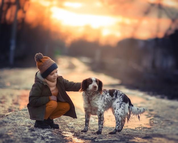 Dziecko wczesną wiosną z psem spacerującym po ulicy