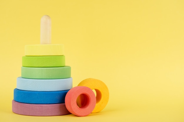 Dziecko wielobarwna piramida na żółtym tle, edukacja dzieci