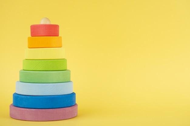 Dziecko wielobarwne piramidy z miejsca kopiowania na żółtym tle