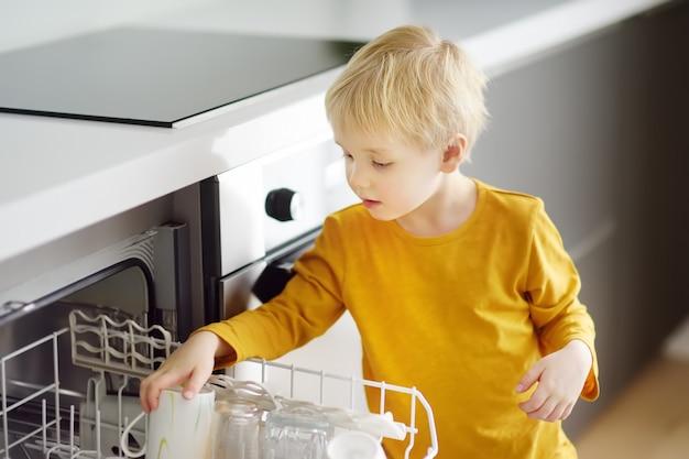 Dziecko wkłada brudne naczynia do domowej zmywarki. zbliżenie.