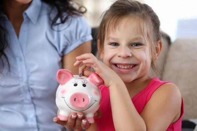 Dziecko wkłada monetę w pudełko oszczędnościowe