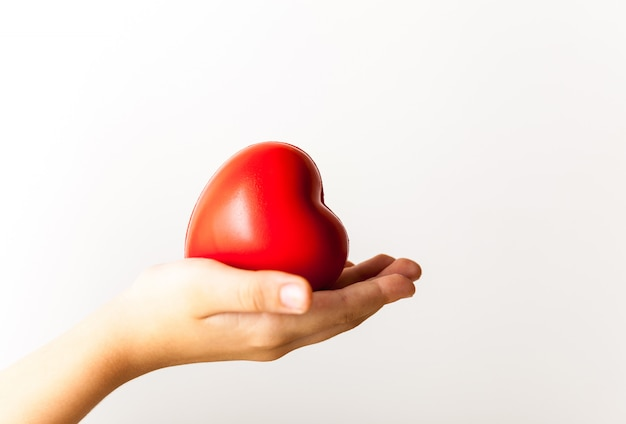 Dziecko wręcza mienia czerwonego serca, opieki zdrowotnej, darowizny i rodzinnego ubezpieczenia pojęcie ,.
