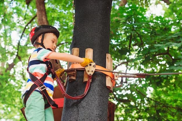 Dziecko wspinające się po linowej drodze. chłopiec nosi kask i wyposażenie ochronne.