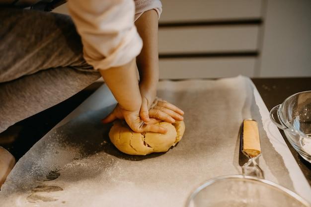 Dziecko wyrabiające ciasto na ciasteczka na papierze do pieczenia