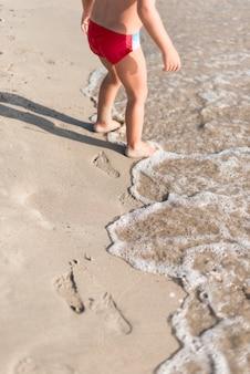 Dziecko wysokiego widoku bawiące się przy brzegu