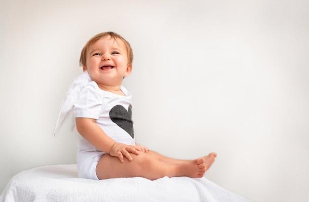 Dziecko z anielskimi skrzydłami i sercem na ciele.