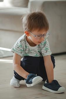 Dziecko z autyzmem w okularach bawi się butami