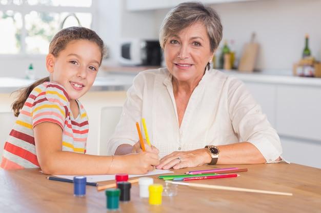Dziecko z babcią patrząc na kamery podczas rysowania