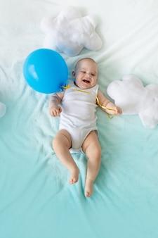 Dziecko z balonem w dłoni na tle błękitnego nieba z chmurami, koncepcja podróży i letnich wakacji