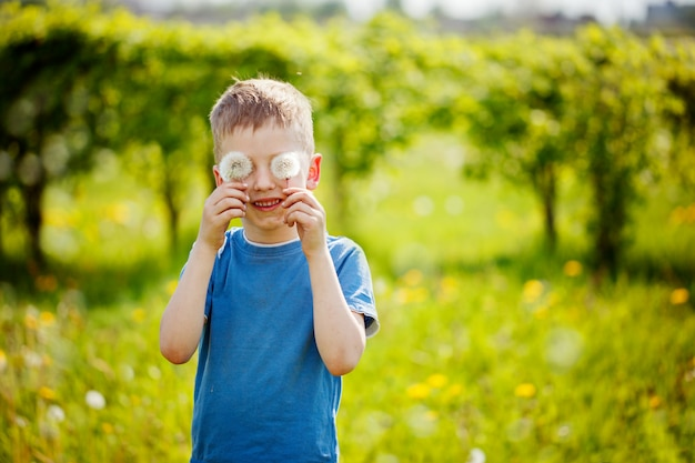 Dziecko z białymi oczami dandeion dmuchanie
